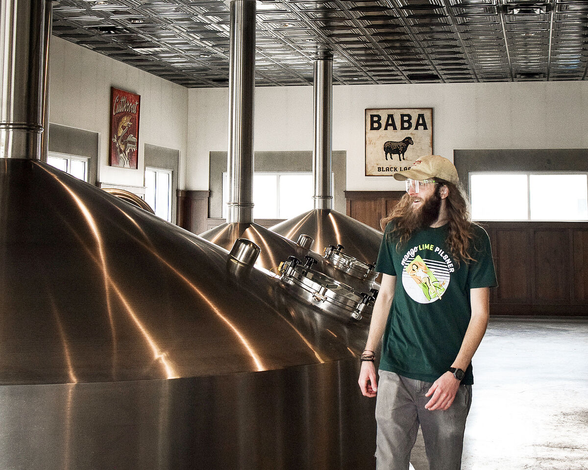 uinta brewer strolls by a fermentation tank in the brewhouse