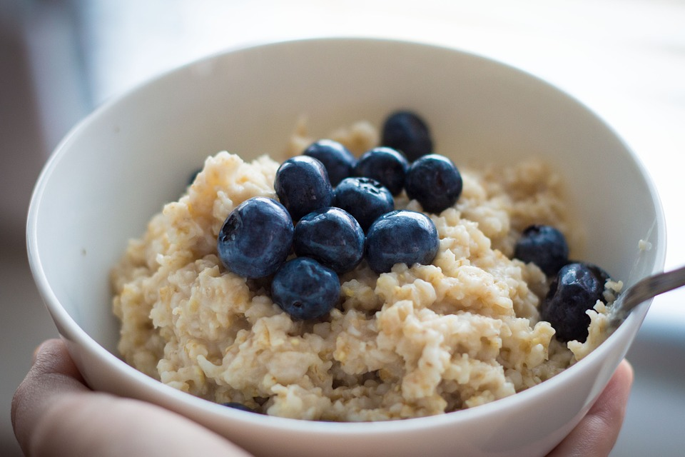 bowl of oatmeal with blueberries on top with a spoon within