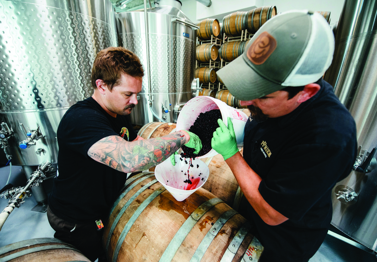 pfriem brewers add berries to a barrel during the brewing process