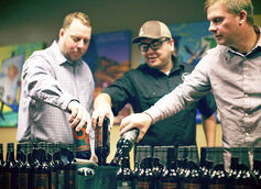 Partner David White (left) with Brewery Production Manager Jason Salas (middle) and Brett VanderKamp dipping 20th Anniversary bottles into wax.