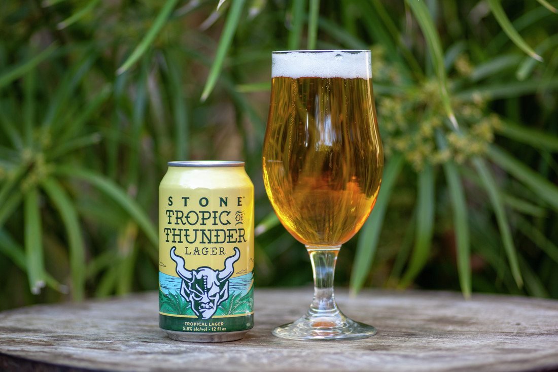 A can and poured glass of Tropic Thunder Lager by Stone Brewing Co.